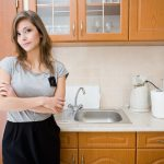 Petite brunette woman standing in kitchen at work