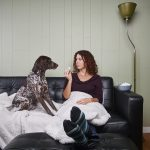 brunette woman sitting on sofa with her dog