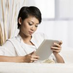 chinese woman sitting on sofa at home using tablet