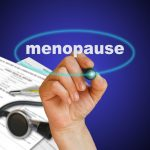 menopause writing with paperwork on blue background