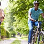 middle age couple riding bicylces in park