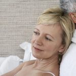 middle aged woman sitting in bed with her back against husband