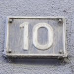 number 10 metal sign on building