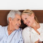 older couple smiling at home in their bed