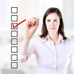 woman wearing white shirt checking off a checklist