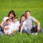 family sitting outside in grass