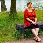 tired middle aged woman outside on park bench