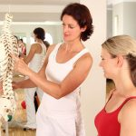 two women discussing bone health in front of a spine