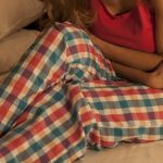 woman in pajamas suffering from abdominal pain