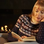 woman inside during winter by fire reading book