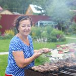 woman outside her home grilling dinner