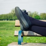 woman resting feet on park bench