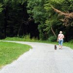 woman walking her dog in state park