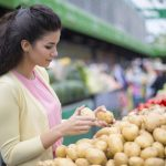 young woman buying potatoes