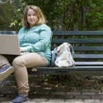 young woman sitting on a bench in a park with a laptop